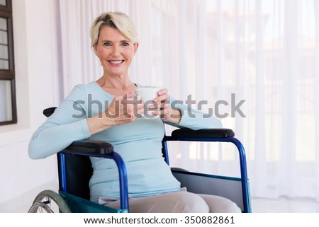happy handicapped senior woman having a cup of coffee in the morning - stock photo