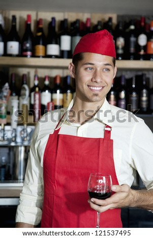 Happy handsome bartender holding glass of wine in bar