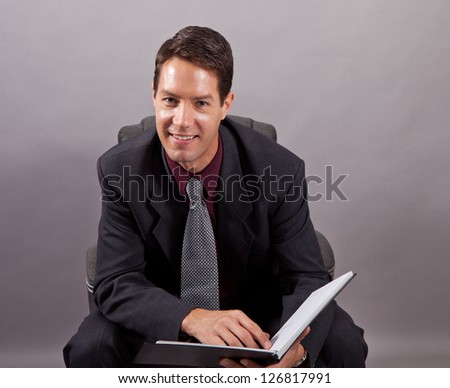 Happy handsome business man isolated on gray