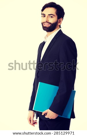 Happy handsome businessman holding a binder. - stock photo