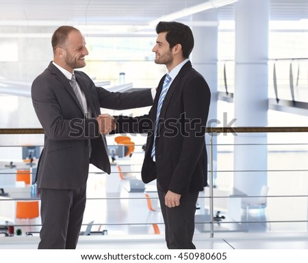 Happy handsome caucasian bristly businessman shaking hands on business deal at office. Hand on shoulder, side view, copyspace, suit. - stock photo