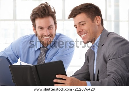 Happy, handsome caucasian businessman looking at personal organizer at business office. Smiling, wearing suit.