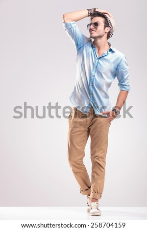 Happy handsome fashion man holding his hand on the hat while looking up, full body picture. - stock photo