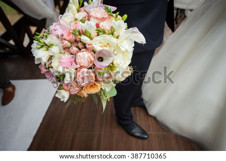 Happy handsome groom with bouquet at wedding ceremony