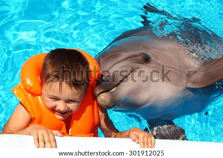 Happy handsome little boy laughing and swimming with dolphin in the blue swimming pool - stock photo
