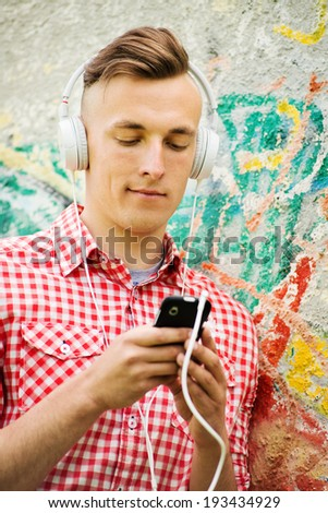 Happy handsome man enjoying his music sitting on the ground against a graffiti covered wall looking up tunes on his MP3 player - stock photo