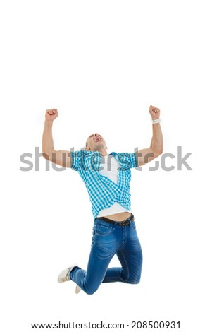 happy handsome man in blue shirt and jeans jumping in the air with his hands raised high up as a sign of success - stock photo