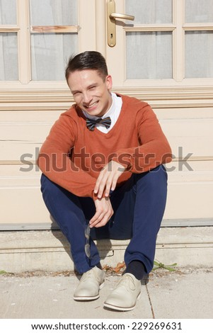 happy handsome man in sweater sitting on steps in front of house and posing , vintage retro photo