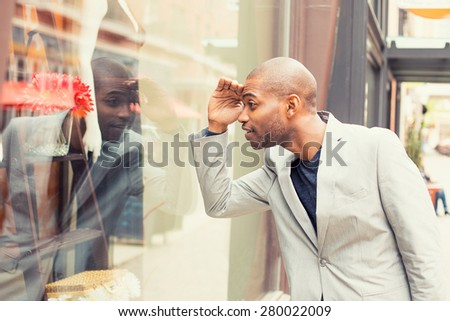 Happy handsome man looking for new clothes. Shopping time - stock photo