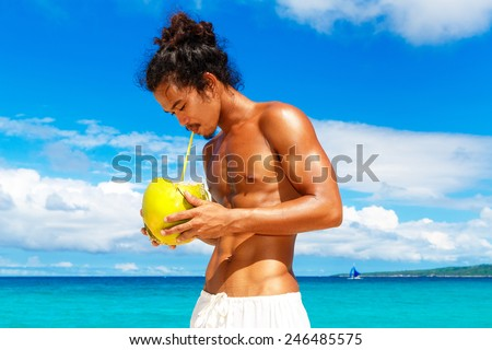 Happy handsome man of Asian appearance with coconut on the tropical beach on sunny summer day during holidays vacation. Tropical sea on the background. - stock photo