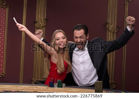 Happy handsome  man  smiling winning and beautiful woman looking at camera  in casino sitting at table with red white and blue piles of chips  waist up - stock photo