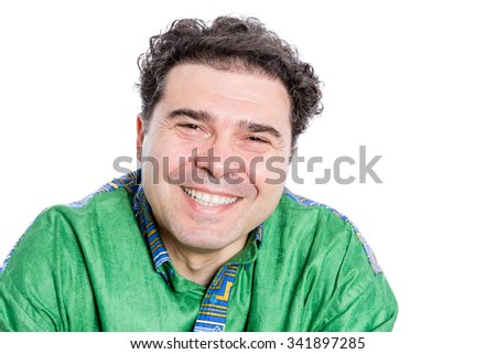 Happy handsome man with curly brown hair wearing a green afro shirt looking at the camera with a wide beaming smile of pleasure and delight, isolated on white - stock photo