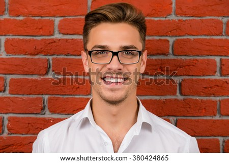 happy  handsome man with glasses smiling and standing near red brick wall - stock photo