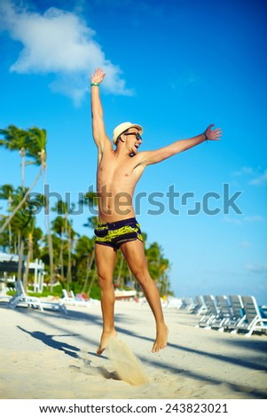 Happy handsome muscled man in sunhat on beach jumping behind blue sky behind blue sky - stock photo