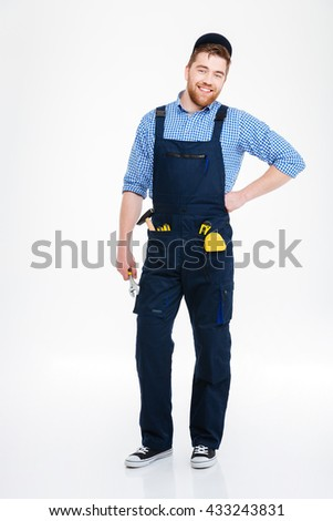 Happy handsome repairman in overall and cap standing and smiling - stock photo