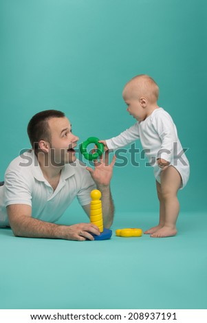 Happy handsome smiling Caucasian father playing with his son baby boy, picking up pyramid circles, isolated on blue. Family fun concept - stock photo