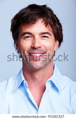 Happy handsome smiling man. Over grey background.
