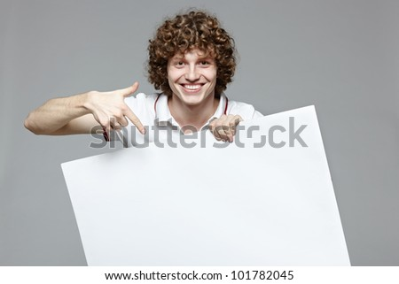 Happy handsome smiling man with banner, over gray background - stock photo