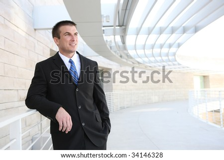 Happy handsome young business man at office building - stock photo