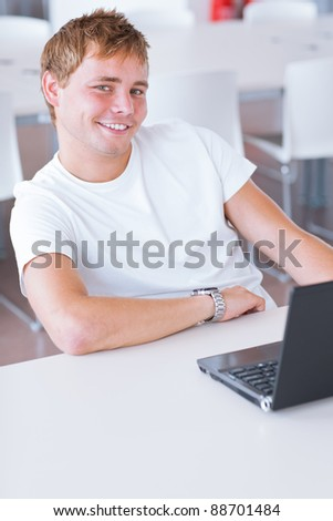 Happy handsome young male college student  using his computer in the campus common area/high school study room (shallow DOF, color toned image) - stock photo