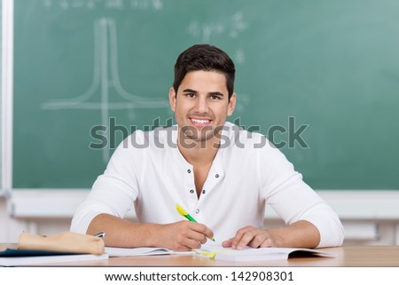 Happy handsome young male university student sitting in front of a blackboard at his desk taking notes looking up at the viewer with a lovely smile