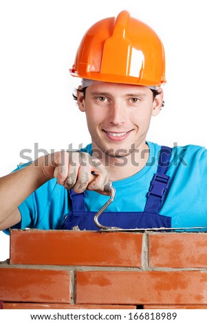 Happy handyman in hardhat with trowel and brick - stock photo