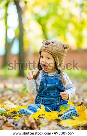 Happy, happy baby sitting in the park with yellow leaves in autumn in bear cap. In autumn park kid sitting in yellow leaves. Cheerful baby sitting in the park in bear cap. Warm autumn day in the park.