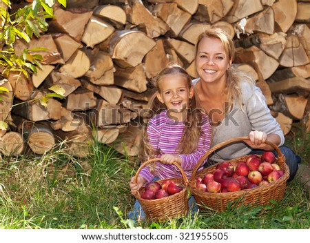 Happy harvesters in autumn - laughing child and woman with red apples in baskets - stock photo