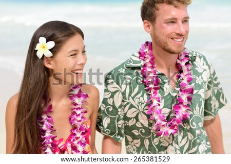 Happy Hawaii beach couple in Aloha Hawaiian shirt. Portrait of Asian woman and Caucasian man on beach walking with flower leis and typical attire for their wedding or honeymoon. - stock photo