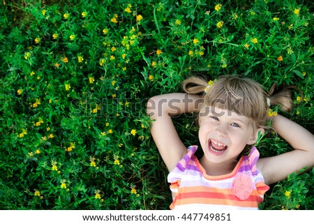 Happy healthy Caucasian girls with heart-shaped hair lying on the grass field background: Little girl child in beautiful green environment Amazing happy sisters - stock photo