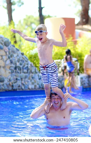 Happy healthy family of two, father and son, laughing teenage boy, having fun together in swimming pool enjoying summer vacation day in aqua park - stock photo