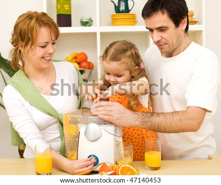 Happy healthy family with a kid making fresh fruit juice in the kitchen
