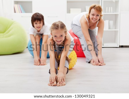 Happy healthy family - woman and kids - doing stretching exercises at home - stock photo