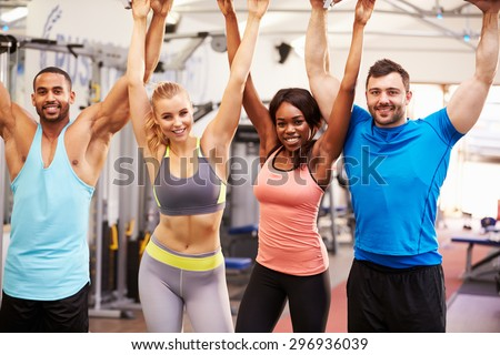 Happy, healthy group of people with arms in the air at a gym - stock photo