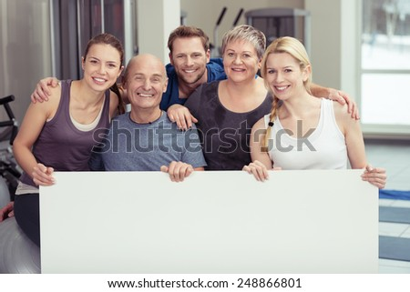 Happy Healthy People Behind Empty White Board While Inside the Fitness Gym. Emphasizing Copy Space for Texts. - stock photo