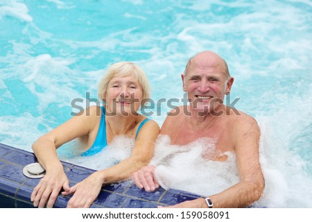 Happy healthy senior couple having fun together in the swimming pool enjoying jacuzzi - stock photo