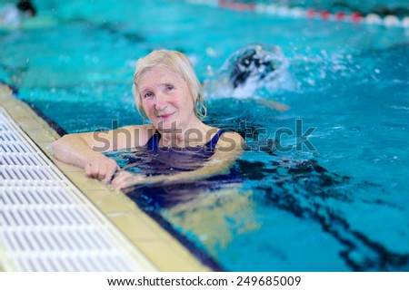 Happy healthy senior woman enjoying sportive lifestyle swimming in the pool - active retirement concept - stock photo