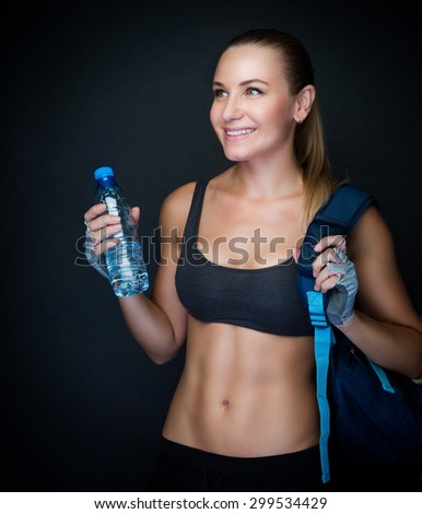 Happy healthy sportive woman over dark background, fitness trainer wearing sexy outfit and holding bottle of water, healthy lifestyle