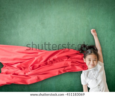 Happy healthy superhero strong powerful little Asian school student girl kid with red scarf dress costume in flying pose on grunge green chalkboard background: Girl power super woman education concept - stock photo