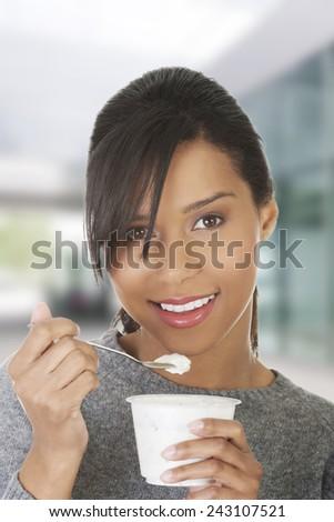 Happy healthy woman eating yoghurt - stock photo