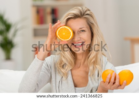 Happy healthy woman playing with fresh ripe oranges holding two in her hand and a third halved fruit to her eye with a lovely smile - stock photo