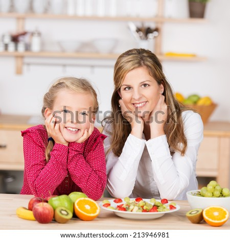 Happy healthy young girl with her mother posing for a portrait together in the kitchen as they prepare a delicious fresh fruit salad together for a healthy diet - stock photo