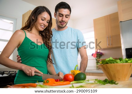 Happy healthy young vegan couple cooking vegetables at home - stock photo