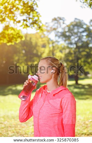 Happy Healthy Young Woman Drinking Water After a Morning Exercise at the Park. - stock photo