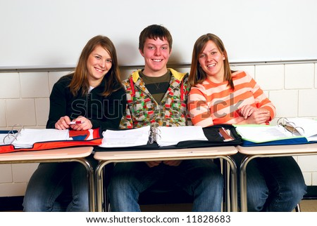 Happy high school students enjoy themselves in class - stock photo