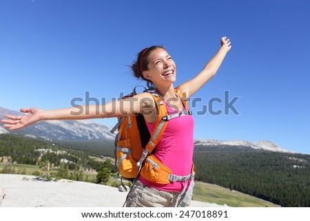Happy hiker girl hiking carefree in nature. Young asian adult showing freedom pose after reaching summit mountain. - stock photo