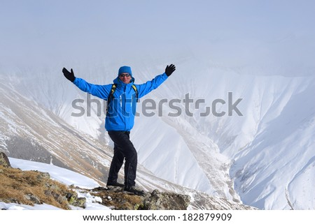 Happy hiker in the winter mountains - stock photo