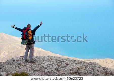 Happy hiker on a stony sea shore enjoys a landscape - stock photo
