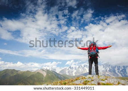 Happy hiker winning reaching life goal, success man at summit. Young hiker holding arms outstretched, freedom and happiness, achievement in mountains - stock photo