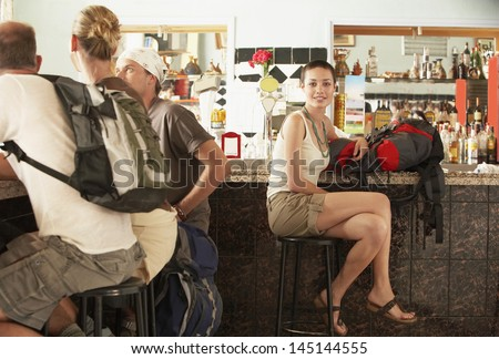 Happy hikers with backpacks sitting in bar - stock photo
